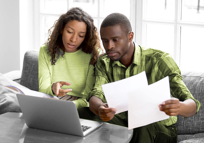 African American couple at laptop with bills